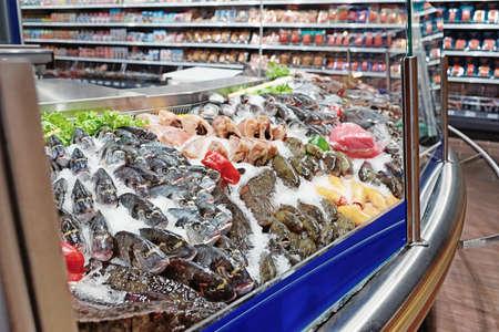 Grande quantità di pesce fresco e frutti di mare sul display del mercato ghiacciato, immagine tonica Archivio Fotografico - 84803904