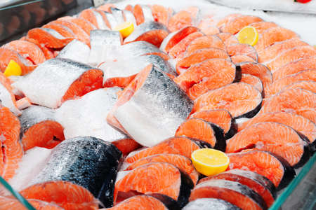 Fresh salmon chunks and steaks on ice in food store, toned image