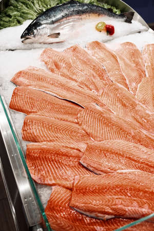 Salmon fillets and whole fish on cooled market display, toned image