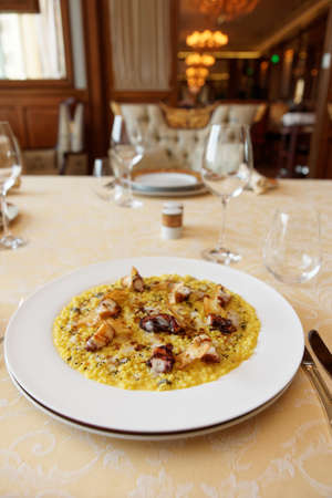 Fregola pasta cooked in risotto style with grilled octopus on restaurant table