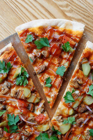 Pizza with meat, pickles and bbq sauce cut in segments and shot from above Stock Photo