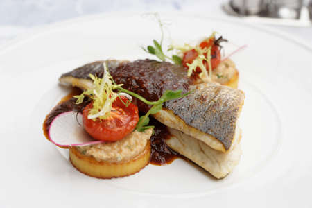Sea bass fillet on white plate, close-up