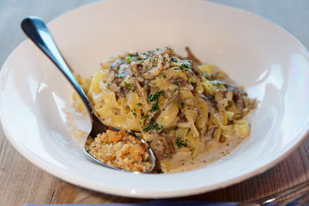 Tagliatelle pasta with cream, mushrooms and spoon of fried breadcrumbs, close-up