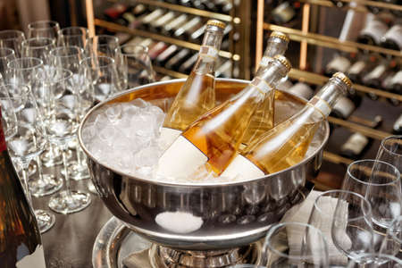 Bottles of Italian organic orange wine resting in bowl with ice, toned, grain added
