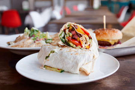 Fast food restaurant dishes, meat and vegetable roll on foreground Stock Photo