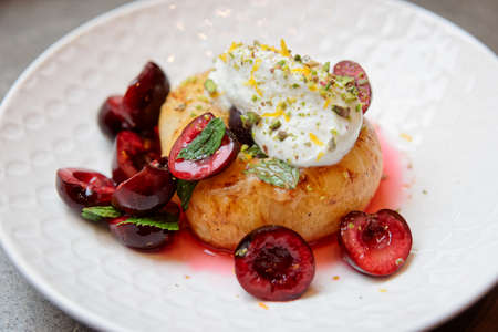 Grilled peach, sweet cherries and whipped cream - healthy fruit dessert