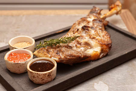 Cooked and fried whole leg of lamb on restaurant table