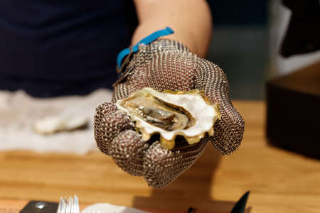 Chef is shoving open oyster in armour gloved hand