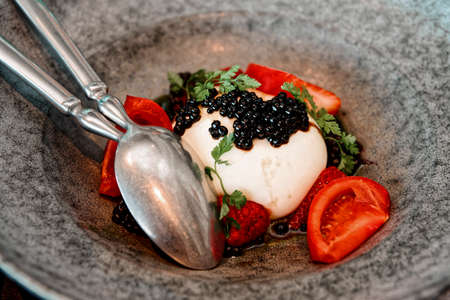 Burrata cheese with seaweed caviar and fruits in stoneware plate, toned image Archivio Fotografico