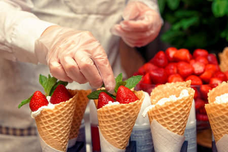 Pastry chef is decorating ice cream with mint and strawberry, toned image