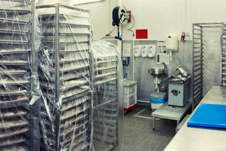 Food processing plant storage room with rack trolleys and hand washing area, toned