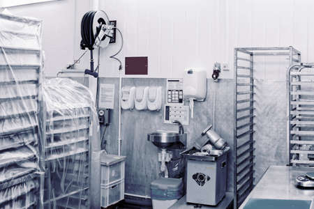 Food processing plant storage room with rack trolleys and hand washing area, toned image
