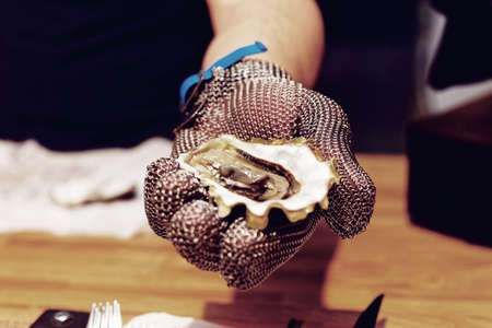 Chef is shoving open oyster in armour gloved hand, toned image Reklamní fotografie