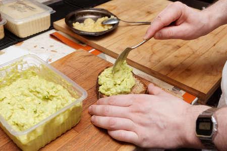 Chef is cooking bruschettas with avocado mash - guacamole sauce Foto de archivo