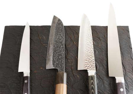 Satz neue und gebrauchte Messer auf schwarzem Holzbrett