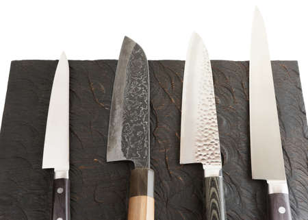 Set nieuwe en gebruikte messen op zwarte houten plank