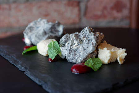 Creative dessert of meringue and biscuit on slate table, close-up Stock Photo