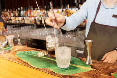 Barman is putting ice ball into drinking glass with pincers, bar counter Banco de Imagens