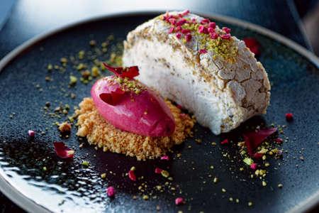 Meringue dessert and fruit ice-cream on dark clay plate