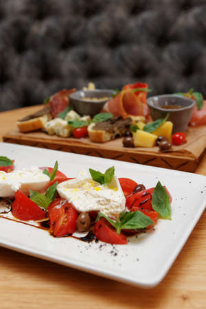 Caprese salad and various snacks in the background, Italian food Stock fotó