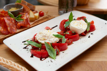 Caprese salad and another food on restaurant table