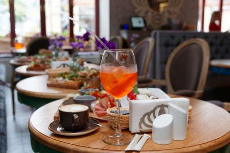 Spritz fizz cocktail and various Italian food on restaurant table