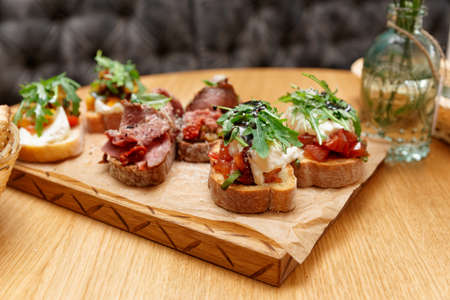Bruschettas with beef and cheese on wooden board, Italian appetizers