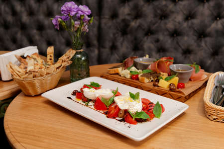 Caprese salad and set of appetizers on restaurant table