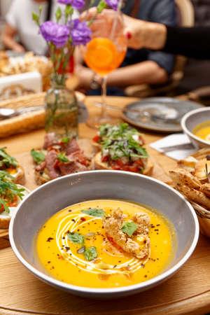 Dining at Italian restaurant, focus on pumpkin soup