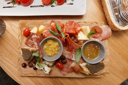 Meat, cheese and another starters on wooden board shot from above