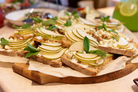 Toasts with blue cheese, pear slices and mint