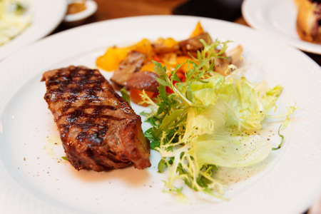 Steak, lettuce and vegetables on plate, close-up Stock fotó