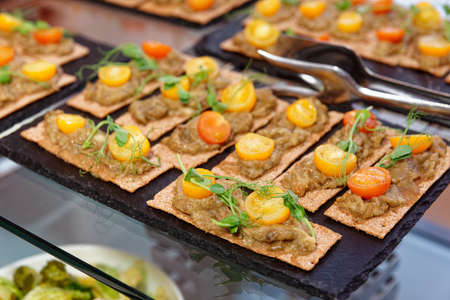 Crisp bran breads with eggplant mash and cherry tomatoes on catering table