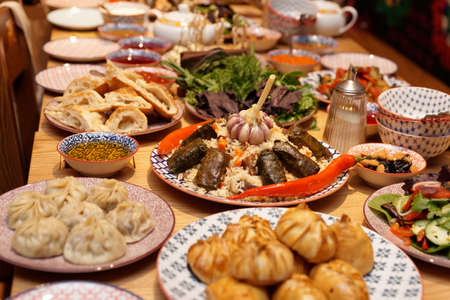Table served with Middle Eastern dishes - pilaf, dolma, dumplings Stock Photo