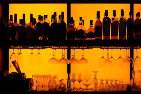 Bottles and glasses sitting on shelf in a bar, back lit, brand names removed