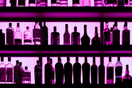 Rows of bottles sitting on shelf in a bar, yellow backlight