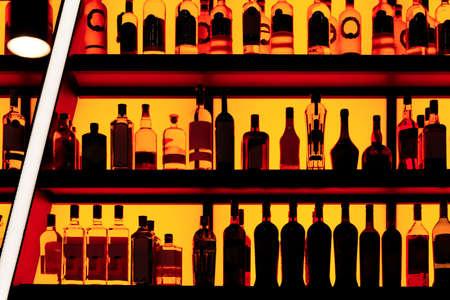 Bottles sitting on shelf in a bar, red neon blacklight