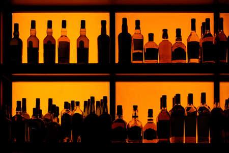 Bottles sitting on shelf in a bar, back lit