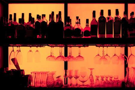 Bottles and glasses sitting on shelf in a bar, back lit, brand names removed Imagens