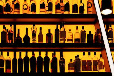 Bottles sitting on shelf in a bar, yellow blacklight