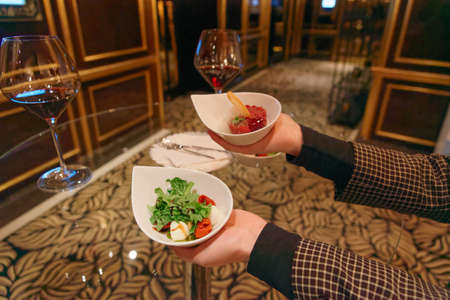 Woman offering steak tartare with froth and Caprese salad at standing reception