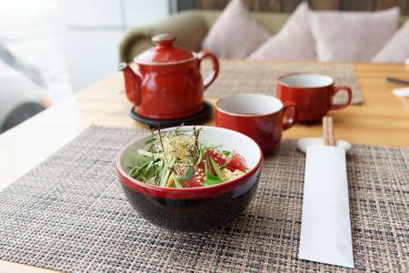 Raw tuna poke bowl and tea on Asian restaurant table