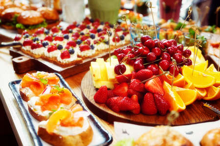 Fruits, berries, fish snacks and dessert on catering restaurant table, toned