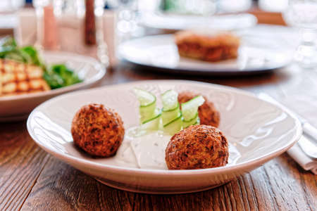 Zucchini croquettes and other dishes on restaurant table, Greek food, toned