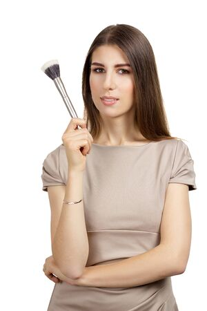 makeup brush: Make-up artist. Young beautiful woman holding make-up brush, isolated.