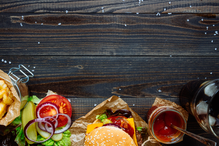 Fresh delicious burgers with french fries, sauce and drink on the wooden table top view, with copy space.