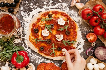 pizza base: Cooking Pizza. Hands adding ingredients to pizza. Pizza ingerdients on the wooden table, top view. Stock Photo