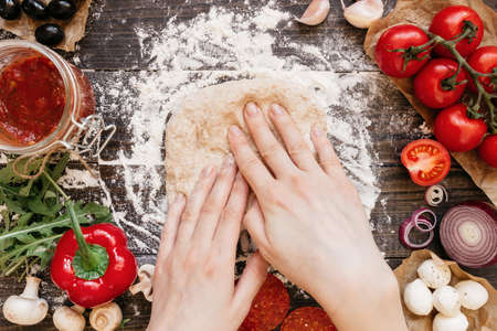pizza base: Woman preparing dough for pizza. Hands kneading dough on the wooden table, top view. Stock Photo