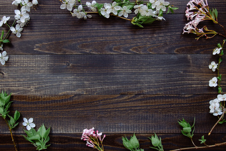Spring background. Beautiful fresh flowers and leaves on the wooden background.