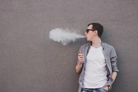 年輕男子吸煙,vaping電子香煙或vape。灰色的背景 版權商用圖片